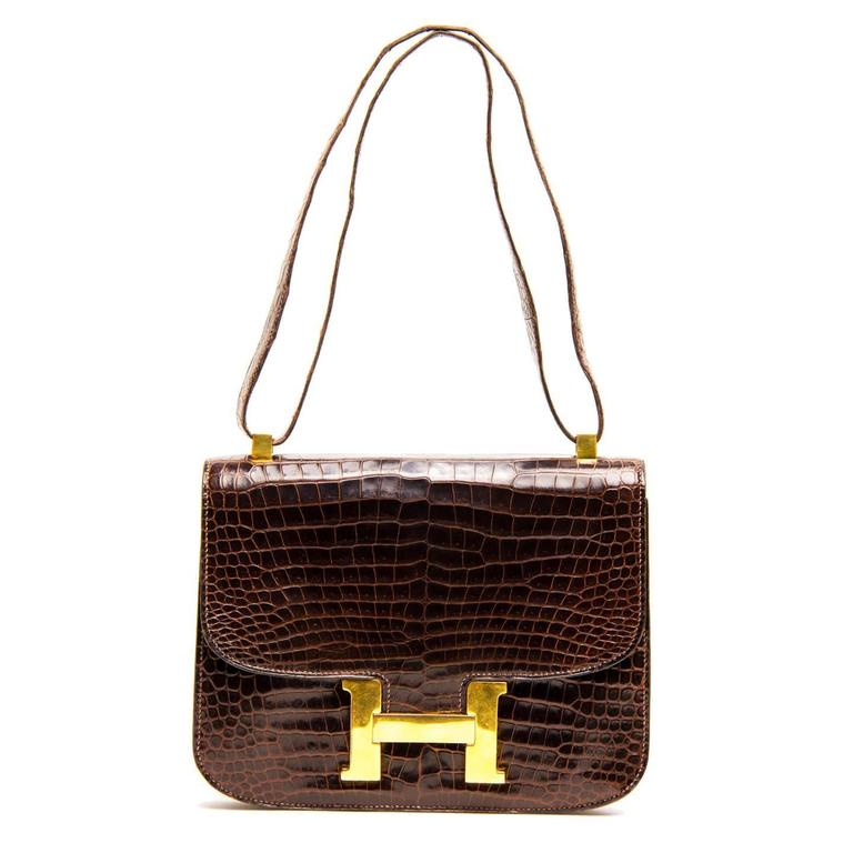 "Brown crocodile Constance 23cm bag with gold hardware. This vintage Hermès style has tonal stitching, a beautiful crocodile skin, a metal ""H"" snap lock closure and a shoulder strap. The interior is lined with brown soft leather with two"