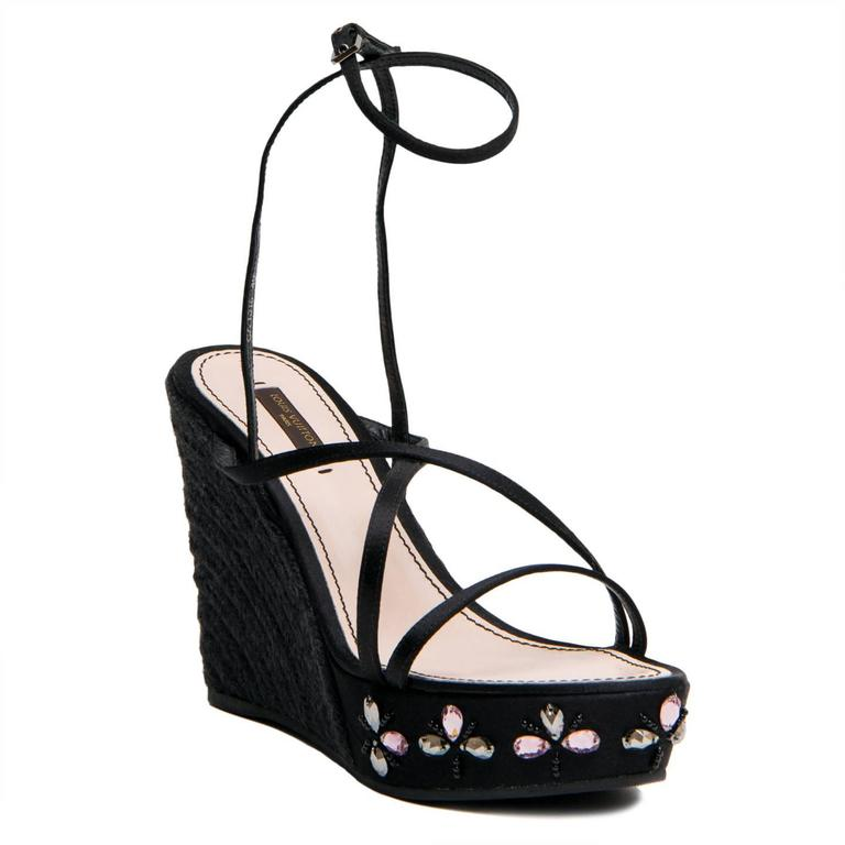 Black satin wedge sandals with crystal decorations to enrich the front and a lace up ankle straps. The wedge is made of jute rope in a beautiful espadrille-inspired style. Made in Spain. Wedges heel: front 3/4