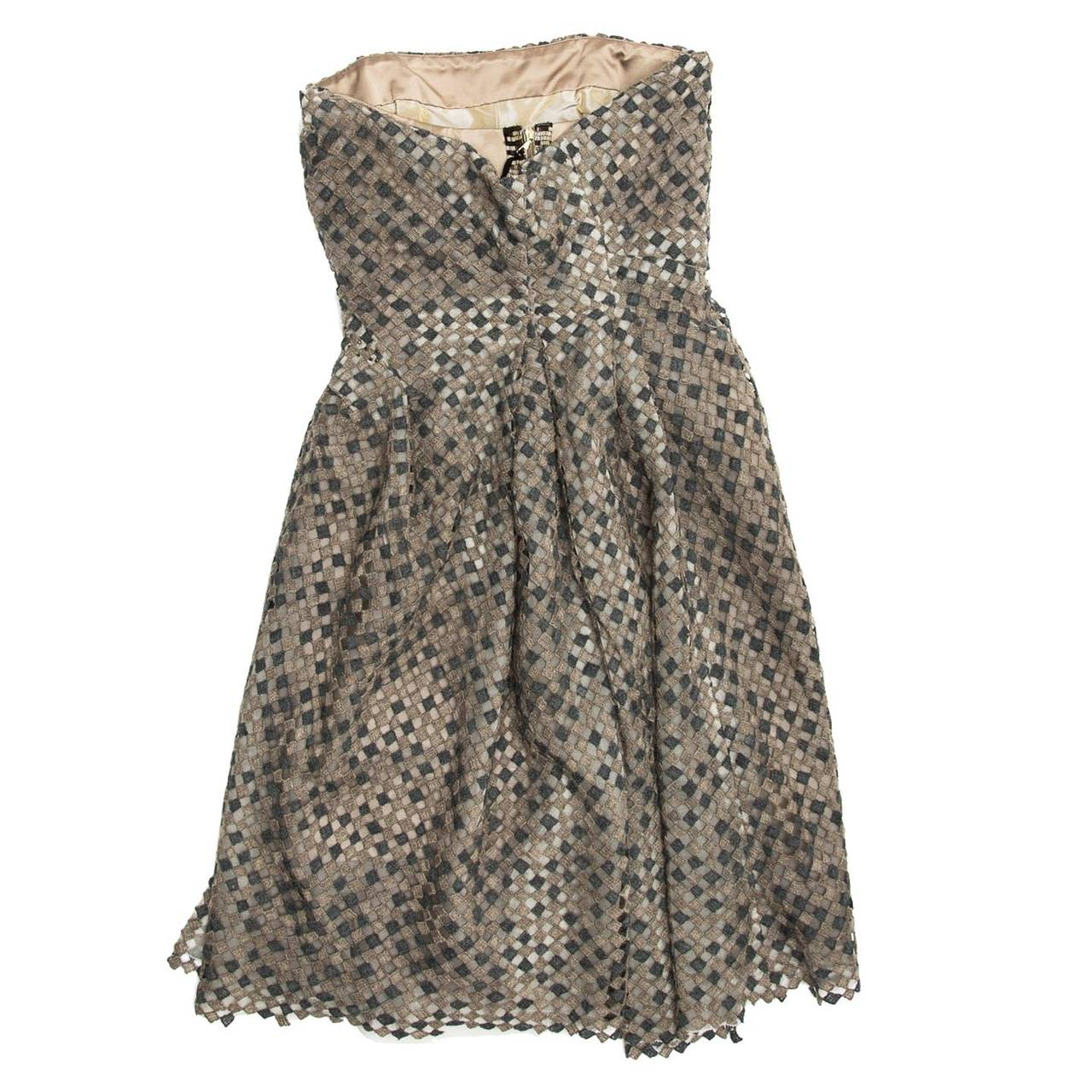 Shades of grey wool/cotton squared texture woven strapless dress. A tan fitted corset gives shape to the top of the dress and a drape enriched by bronze round beads on the left hip creates movement to the A-shape skirt. Dark grey beads embellish the