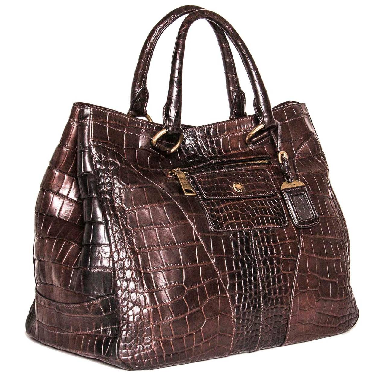 Burgundy distressed crocodile large bag with brass details. The leather is beautifully applied with round cuts on front and back corners, which make the bag look very elegant. Two chunky zippers follow the shape of the leather cuts at back, while
