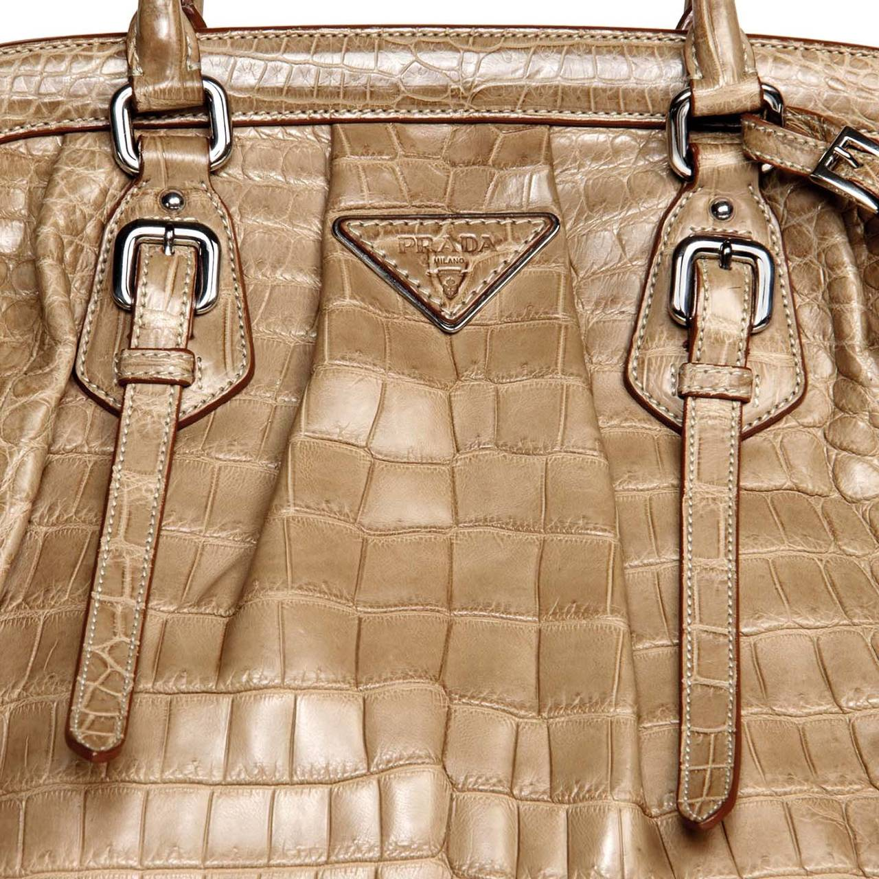 Light brown crocodile bag with a vintage classic design, style reference number BR 3511. Front and back are enriched by extra straps with little belt buckles and pleats that emphasize the round volume of the bag. The front of the bag is also