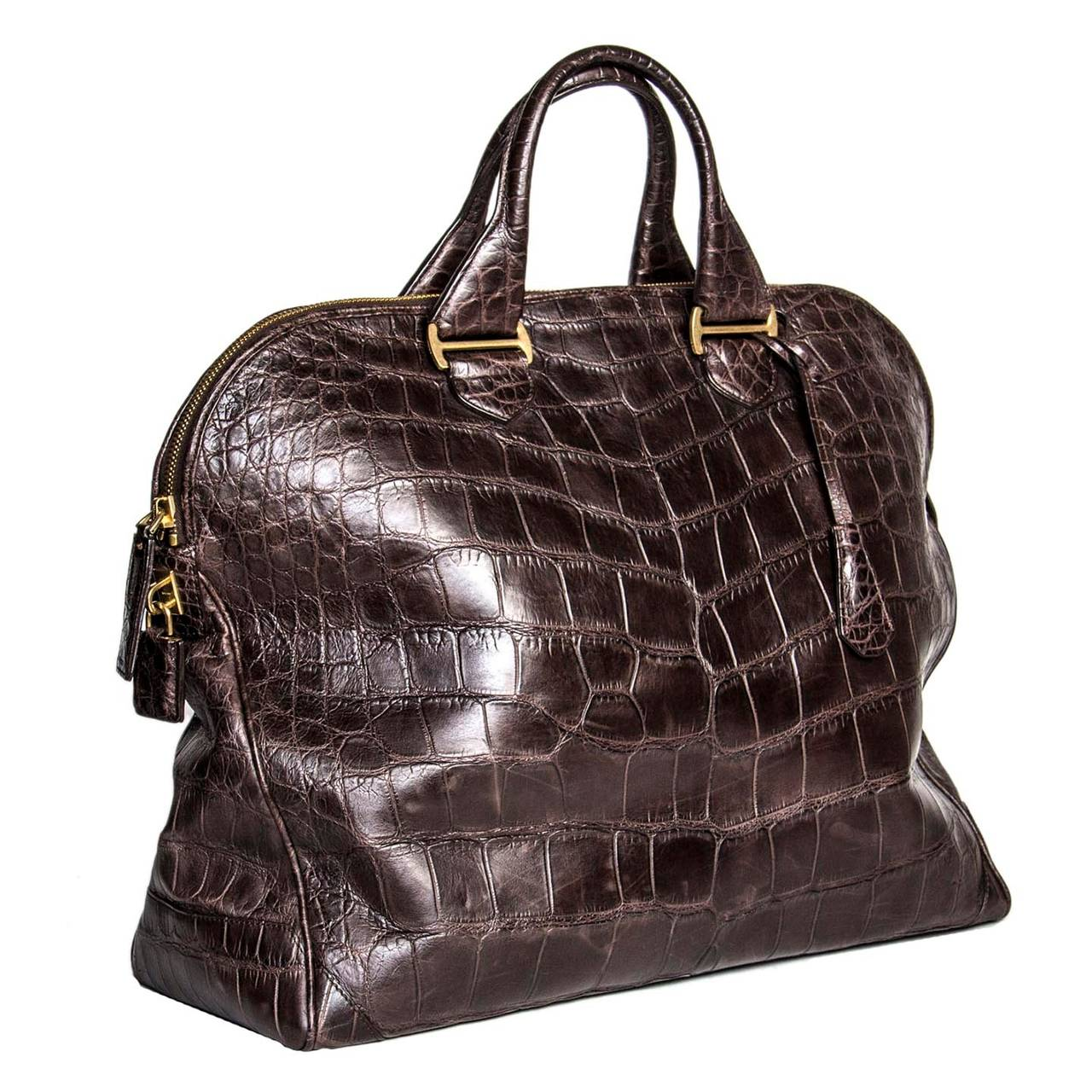 "Beautiful chocolate brown crocodile oversized bag with brass chunky zipper and details. The bag also has matching brass and crocodile lock and key. Bought in Zurich at the opening of the Tom Ford Store. Size : H 19"" L 23"" W 8.5"""