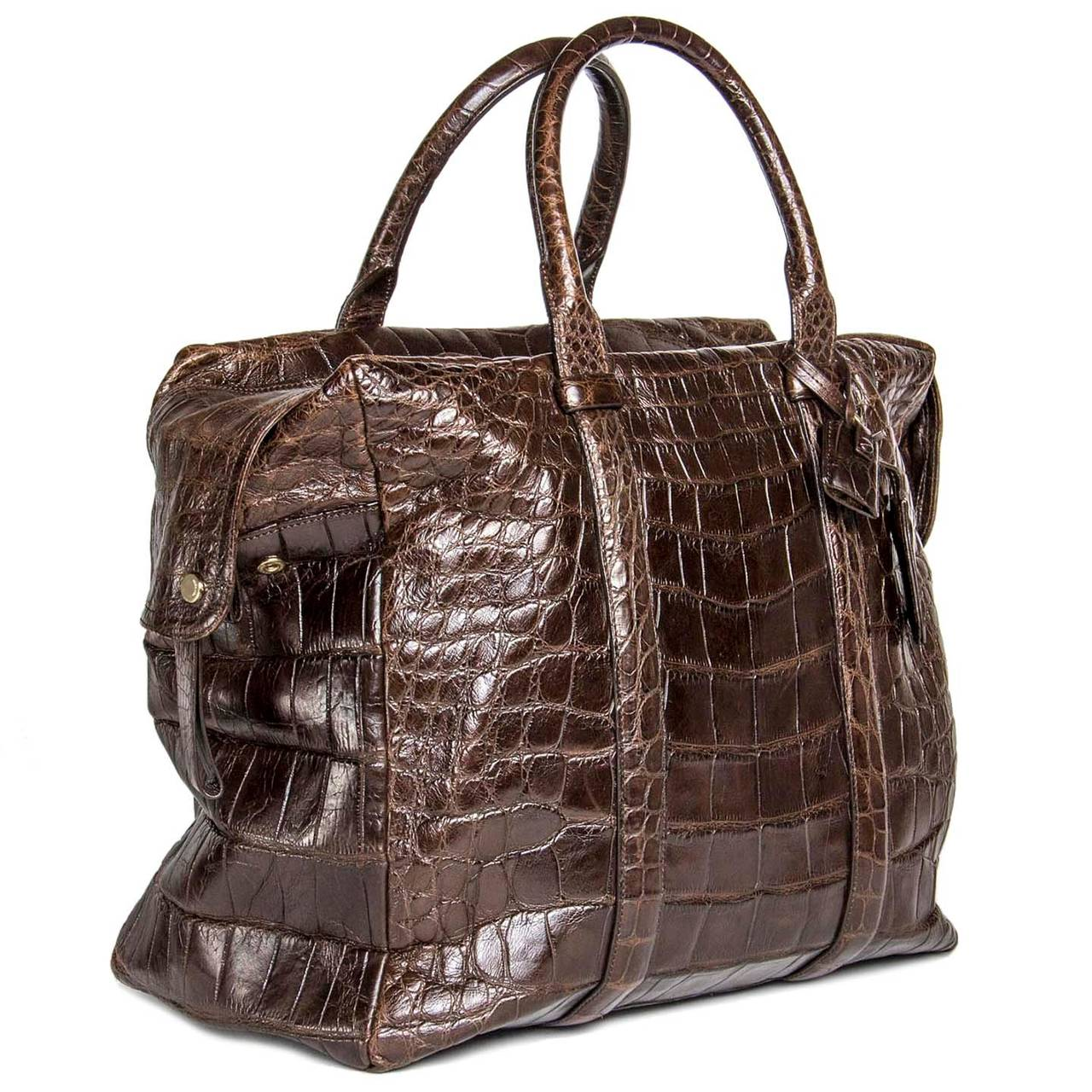 Chocolate brown crocodile oversized bag with wide flap zipper cover that closes with brass snaps. The shoulder straps were extended to go around the bag and decorate front and back. The bag also has matching brass and crocodile lock and key.