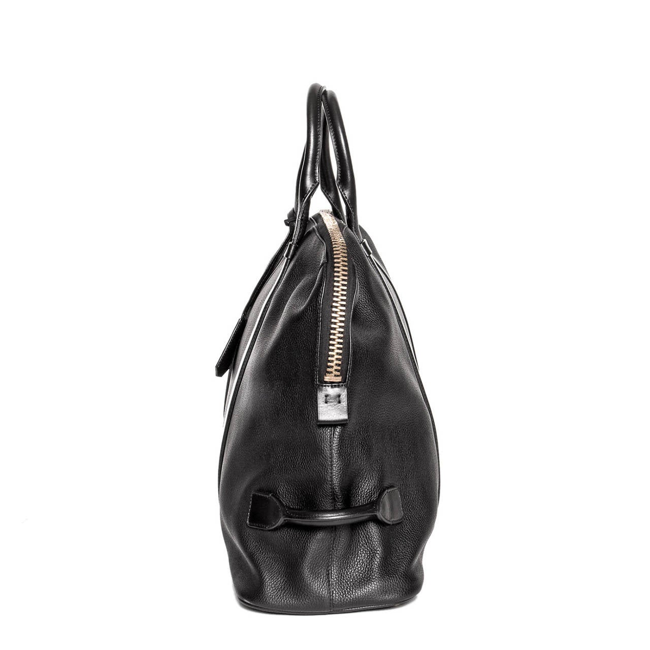 Black textured leather oversize/travel bag with an exaggerated bronze metal zipper with a black leather puller and handle on one side. The shoulder straps are made of smooth leather and extend to front and back panels. The bag has also a matching