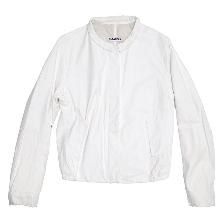 Beautiful soft white leather bomber style jacket with a small peter pan collar. The front fastens with caramel color buttons concealed under a leather flap. The side pockets also fasten with matching buttons concealed under flaps.