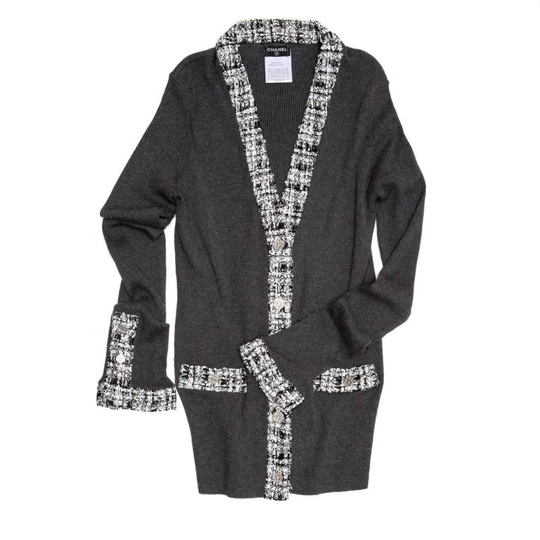 Grey cotton ribbed knit cardigan with black & white tweed inserts at V-neck, button flaps, cuffs and pocket. The cuffs have a shirt opening detail with 3 Chanel logo metal buttons to match the ones at center front and pockets. The fit is quite