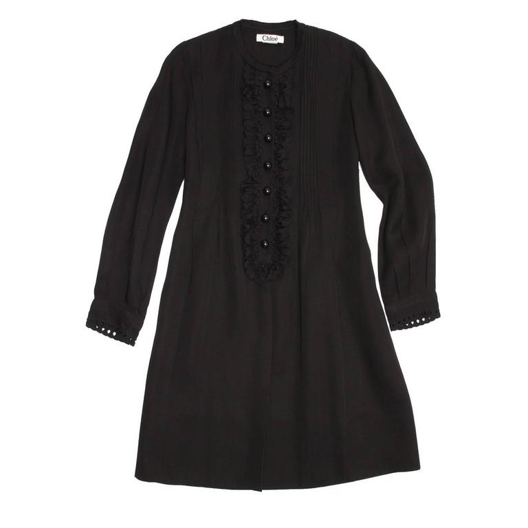 Black cotton/linen knee length dress with fixed little pleats and flower appliqués at front bib and cuffs. The Nehru collar has raw edges and large ball buttons fasten the front top. A black elastic tape holds the waist line at back.