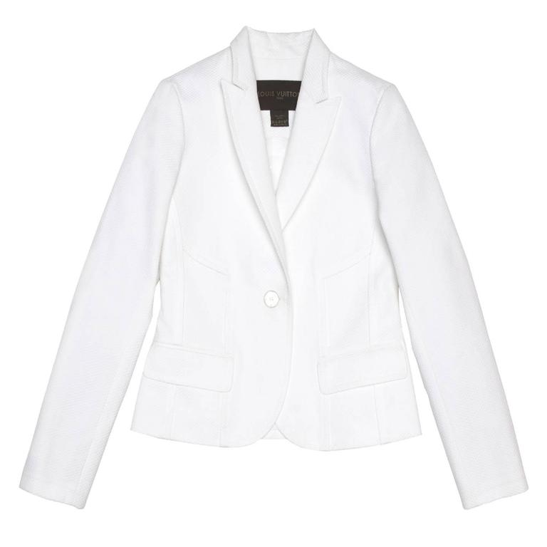Beautiful white cotton pique short fitted blazer with peaked lapel and rounded front hem. All the seams on the jacket are folded toward the outside and create geometrical effects with a combinations of curves and straight lines. The front is also