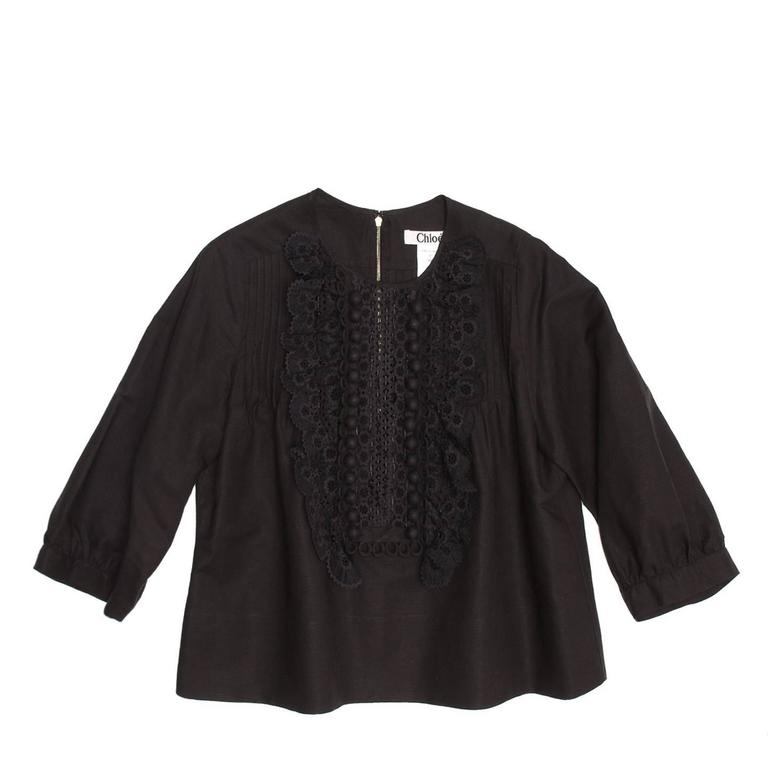 Black linen top with front bib beautifully decorated with fixed pleats, cotton lace, trims and linen covered little balls. The back is also enriched by fixed small pleats and a gold color metallic zip.  Size  40 French sizing  Condition