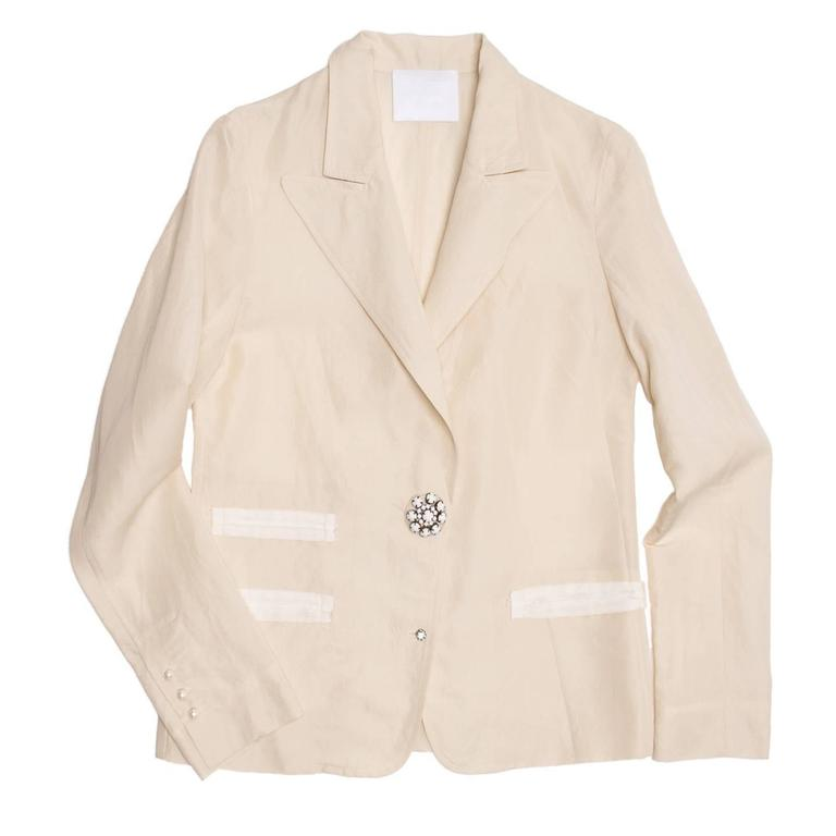 Lanvin 2008. Cream colored raw silk blazer with three slit pockets defined by ivory grosgrain ribbons. Small round perl buttons adorn the cuffs and a big white stone jewel button together with a little silver rhinestone flower button fasten and