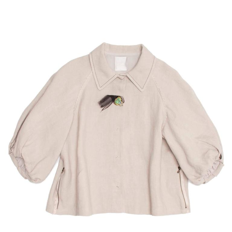 Lanvin 2006. Ecru linen cropped A-shape jacket with 3/4 raglan cut sleeves enriched by raw edge seams embellished by tone-on-tone decorating top stitches and puffy cuffs. The top stitches on the peter pan collar are black to create contrast and