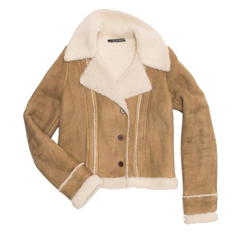 Lambskin suede cropped jacket with shearling lining, collar, cuffs, hem and seam details. The fit is quite tight thanks to the front and back darts that are emphasized by a leather tape and white shearling. The front has a small double breast