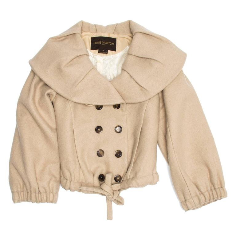 Beige wool and mohair blend cropped jacket with double breast opening and shawl collar. The collar is wide and adorned with fixed pleats while the cuffs are gathered as well as the the hem at front, which also has a self-fabric tie. Slash pockets