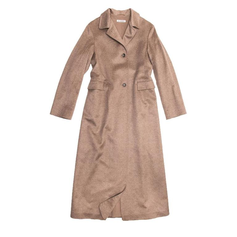 Camel color, cashmere and mink hair floor length coat. Convertible collar which can be worn open or closed, on a single breasted closure with three dark brown buttons. Two front pockets with squared flaps. Adjustable belt visible only at