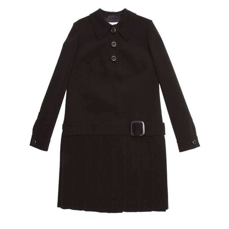 Black thick triacetate/polyester blend 60's style dress with open back and pleated skirt. The shirt collar is quite wide and pointed, the front opening stops at bust and fastens with three large black buttons. The dress has a straight line with a