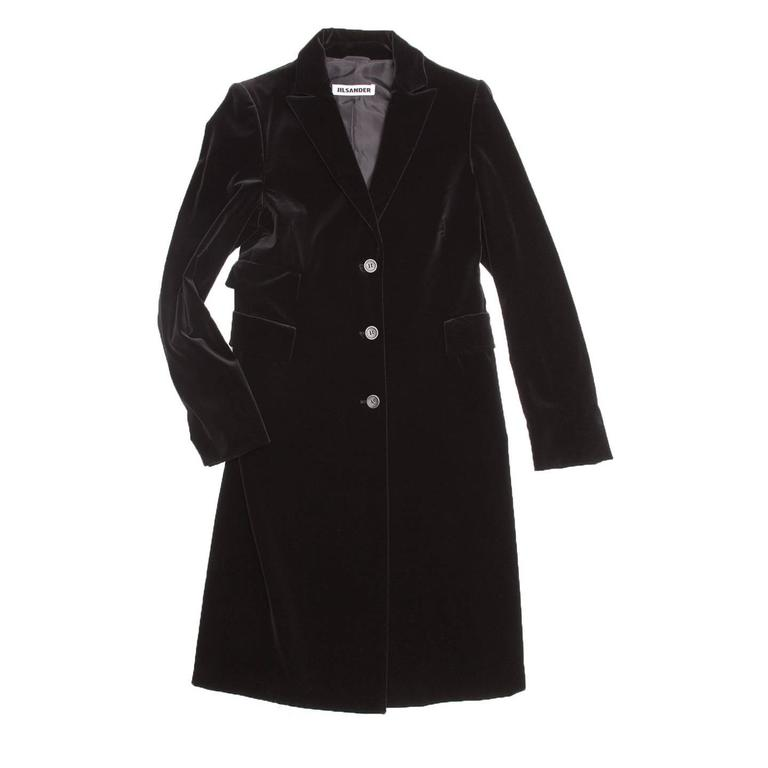 Black cotton velvet knee length coat. Small peaked lapel, three front pockets with squared elegant flaps. Single breasted closure with three buttons. Long back vent starting at hips.  Size  40 French sizing  Condition  Excellent: never worn
