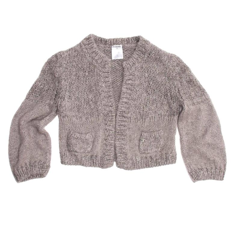 Melange grey angora/cashmere/chinchilla blend cropped cardigan with free open front. The collar has a classic Chanel round line and two mini patch pockets enriched by a beautiful jewel Chanel logo prettify the front of the cardigan.  Size  42 French