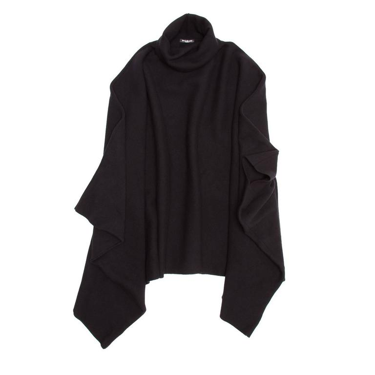 Black wool & cashmere poncho with roll neck and two front hidden pockets. The fit is very wide, mid-length and the sides are closed leaving an opening only for the arms. Made in France.