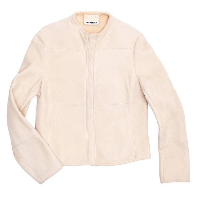 Cream shearling collarless racer style jacket with  tone-one tone hidden zipper at center front.