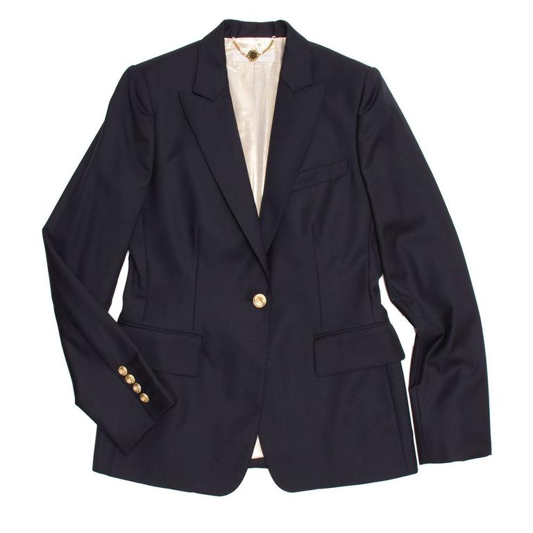 Navy wool single button tailored blazer. Gold buttons at front opening and at back of cuffs. 2 flap pockets at front and handkerchief pocket at chest. Pick stitching detail around the lapels. Vent at center back bottom. Chain hanger loop with logo