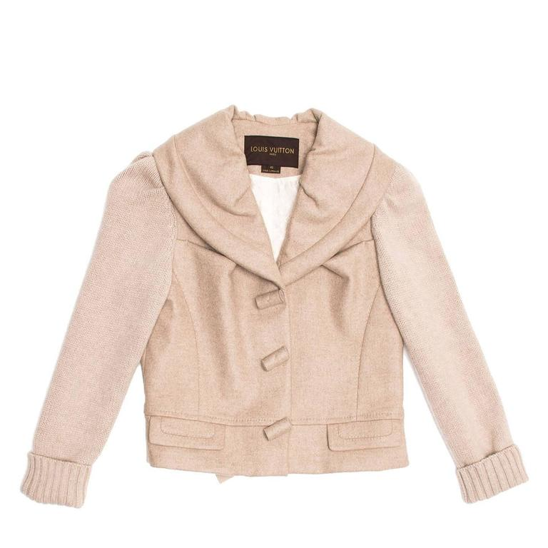 Ecru waist length cashmere jacket with knit sleeves and shawl collar. Cashmere toggle style buttons fasten the front opening and two squared pockets with flaps sit at waist.The back hem width is adjustable with a ribbon tied inside the jacket and