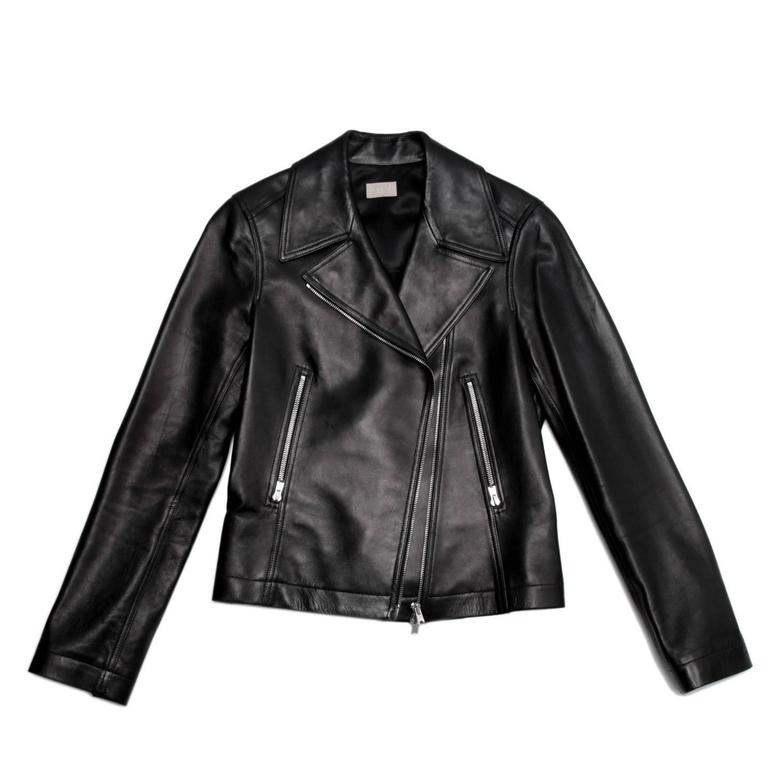 Black lambskin leather motorcycle style jacket with silver metal zipper front pockets that mach the center front zipper and those at cuffs. The back darts form closed vents at bust, they are fixed at waist and then open at hem as inverted pleats. A