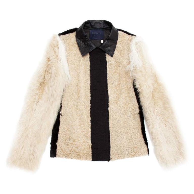 Hips length unique jacket made of beige and black lamb fur with black textured wool inserts at front, back sleeves and under collar. The fur on the body is short while it's longer on the sleeves. A thin and soft ivory longer goat fur insert