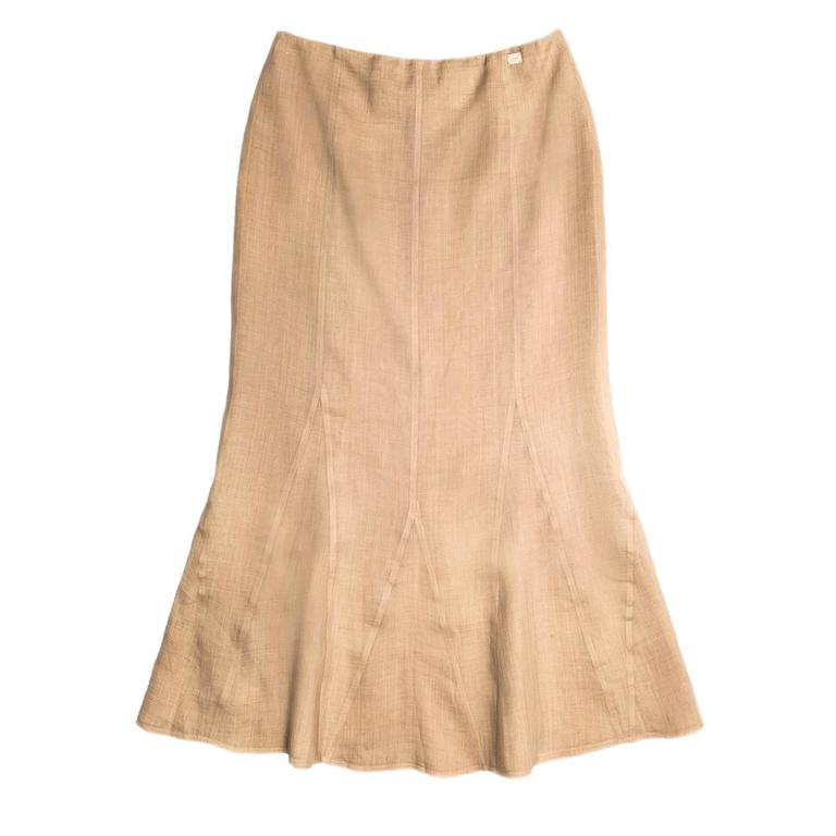 Ankle length tan ramie skirt fitted from waist to knees, with flare at hem thanks to the godet inserts. The color is natural echru, the fabric light and a sheer, for this reason the skirt is composed of two layers. A small Chanel placket is sewn at