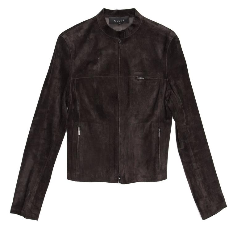 Chocolate brown suede cropped jacket with open ended metal zipper at center front and standing collar that fastens with a dark metal snap button. More metal zippers enrich the pockets at waist, the breast pocket, the cuffs openings and the back