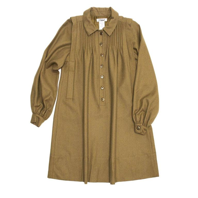 Army green wool 60's style A-line shirt dress with classic shirt collar and front opening with brushed bronze metal buttons. Small fixed pleats enrich the back yoke and the front shoulders, which are also decorated by a deep fixed pleat that starts