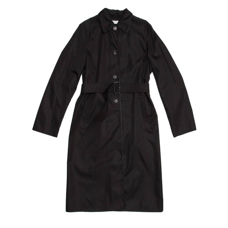 Black nylon knee length raincoat with leather piping around the peter pan collar and front opening. The front fastens with 4 buttons and a belt tighten at waist.  Size  44 Italian sizing  Condition  Excellent: worn a few times