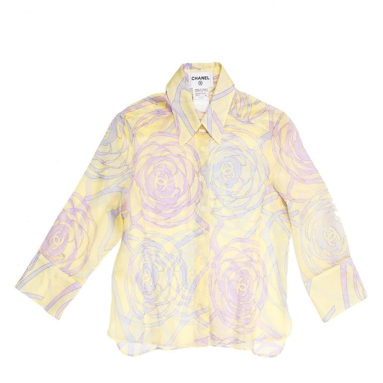 Yellow sheer cotton short shirt with purple and violet geometric floral print with Chanel logos. The sleeves are 3/4 length that fasten with beautiful mother-of-pearl floral cufflinks, the hem is straight with vents at sides.  Made in France.  Size
