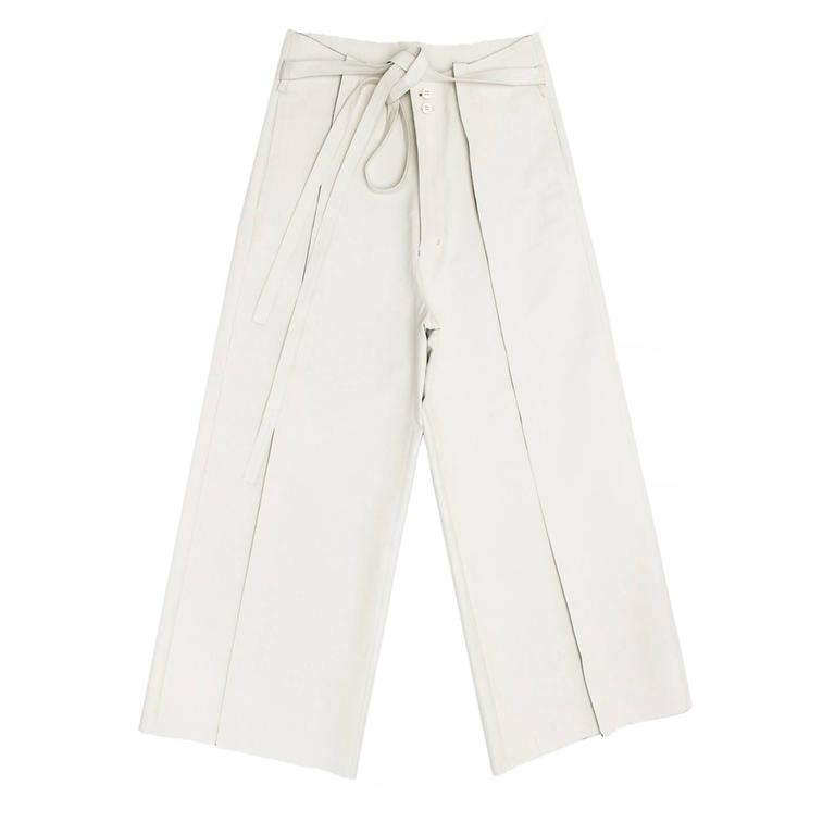 Ivory thick color cotton & polyester blend gaucho slack trousers with very wide legs and tie-up self-fabric belt. The pants have a front unique insert with raw edge finishing and tone-on-tone top stitching where the pleat is supposed to be. The