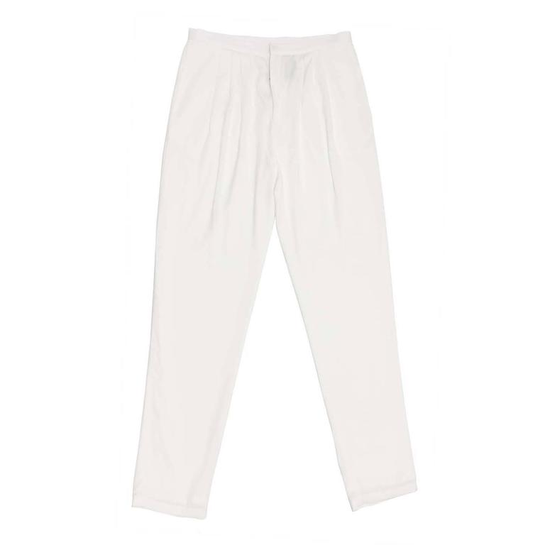 White light trousers wide at hip and narrow at the ankles. The pleats under waist at front create soft volume on the top part, the waist band is thin and simple, slash pockets sit on the side seams and slit pockets enrich the back. Made in