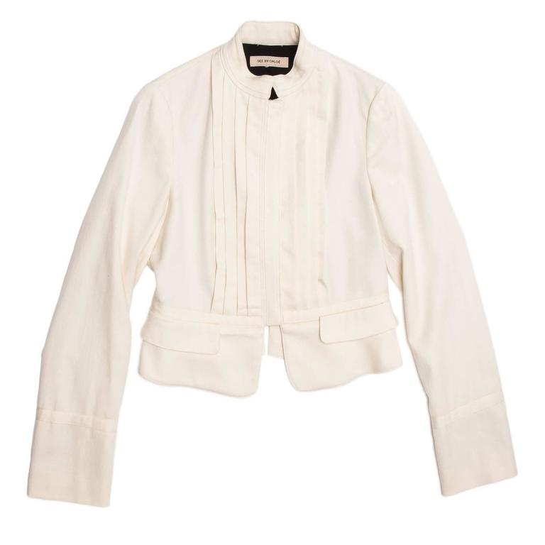 Cream wool/cotton cropped bellboy style jacket with pleated front detail and tone-on-tone binding on neck, cuffs, waist line, front opening and back seams. The jacket fastens at center front with concealed metal snap buttons.  Size  46 Italian