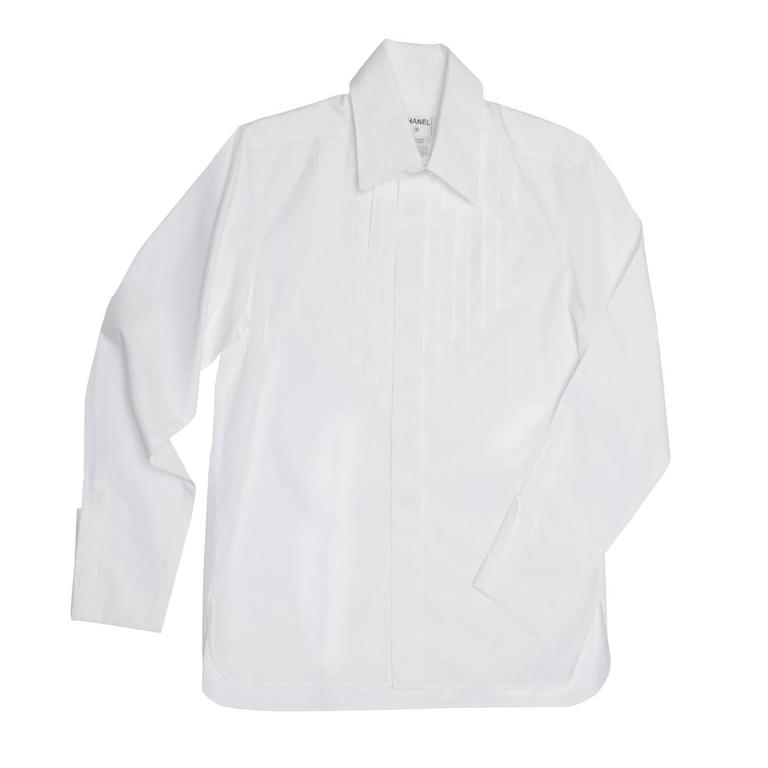 Pure white cotton shirt with large rounded peter pan collar standing on a higher neck that fastens with two white and metal buttons. The buttons at center front are hidden under a wide placket and a bib detail repeats this detail with vertical and