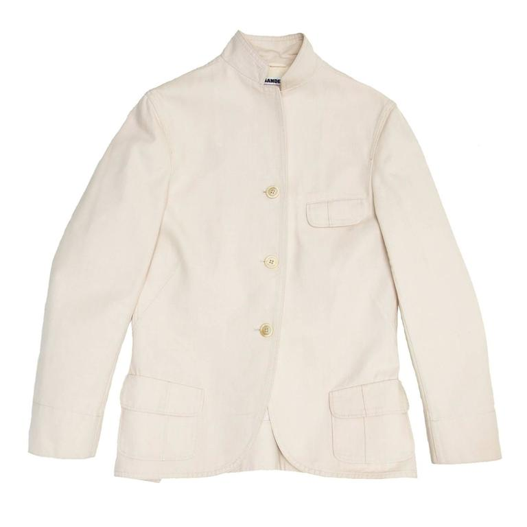 Ivory cotton jacket with a 3 button closure and small lapel. The blazer has a quite long casual style, with a little flap pocket at bust and slanted flap pockets on patch pockets at waist. The back vents are a continuation of the front darts, they