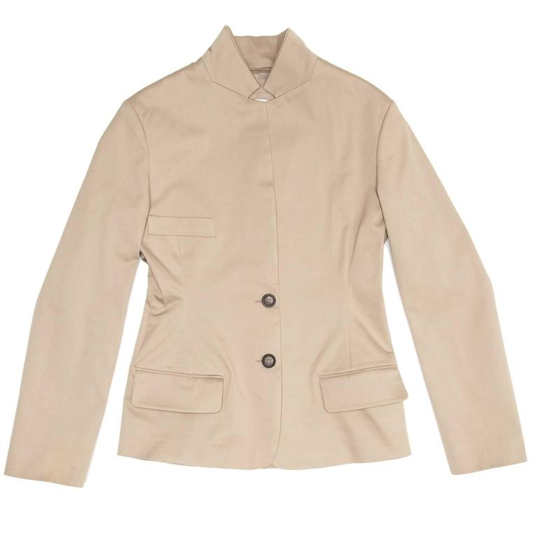 Taupe single breasted cotton jacket that fastens with 2 dark buttons at waist leaving a long lapel. The shape is fitted, the front enriched by a classic breast pockets and two flap pockets at hips, while the back has a long shapes vent that starts