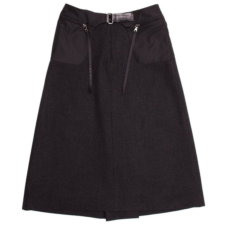 Prada Charcoal grey wool A-line skirt with black nylon round patch pockets on top-sides that open at front with metallic zippers adorned by dangling ribbons. The pockets join at front waist with a black leather insert that fastens with a silver