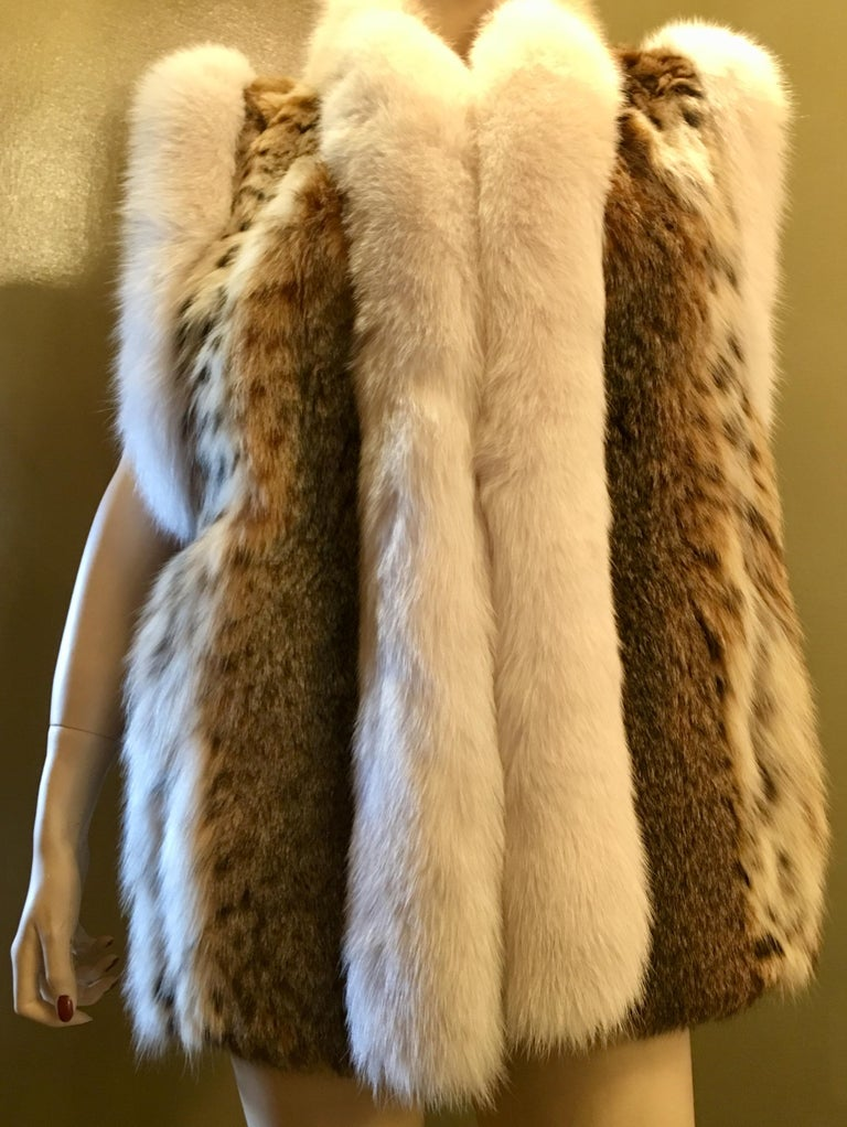 Strikingly marked lynx fur vest with vivid coloration, contrasts with white fox fur trim around the arm openings and the front edges.  The pelts are very soft and silky to the touch.  Features velvet-lined slash pockets and a satiny, taupe colored