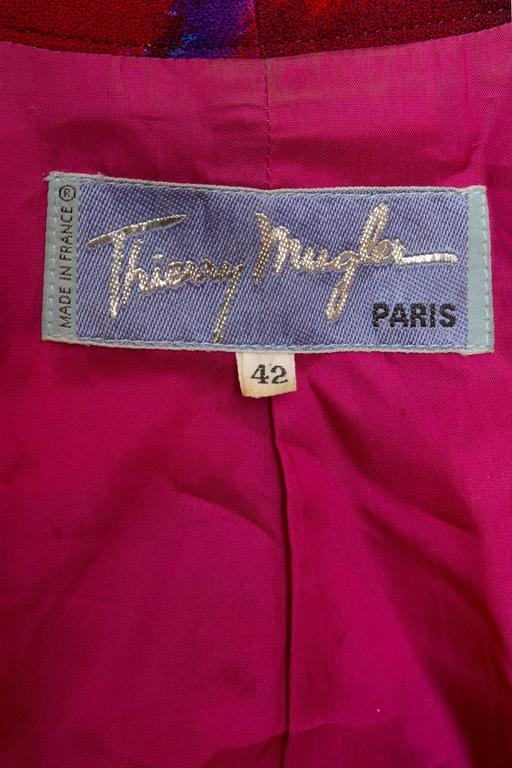 A stunning 1980s Thierry Mugler wool blazer with an asymmetrical hemline and a push button closure. The blazer have long tapered sleeves with structured shoulders held in place by shoulder-pads. The color combination is absolutely stunning and the