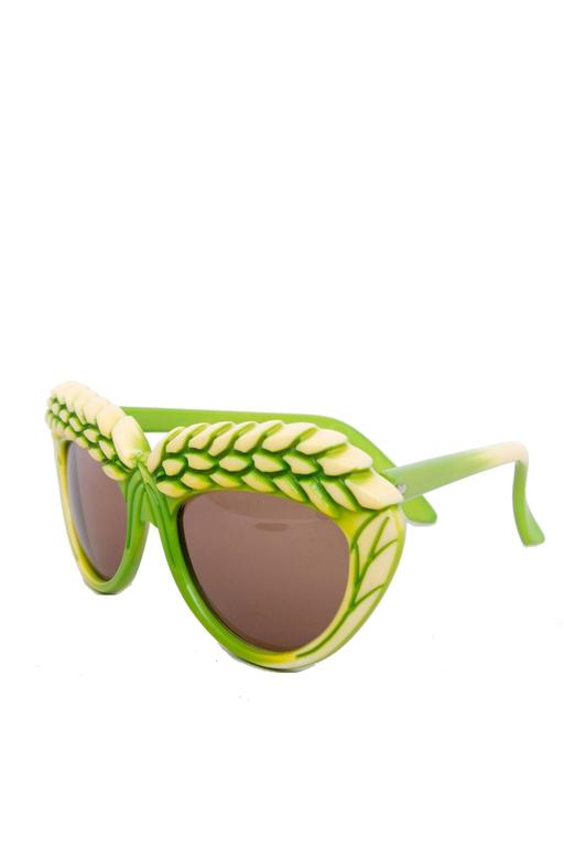 A rare, bright pair of 1980s green Isabel Canovas sunglasses with brown tinted lenses  and a detailed frame, where two yellow barley heads stretch across each lens.