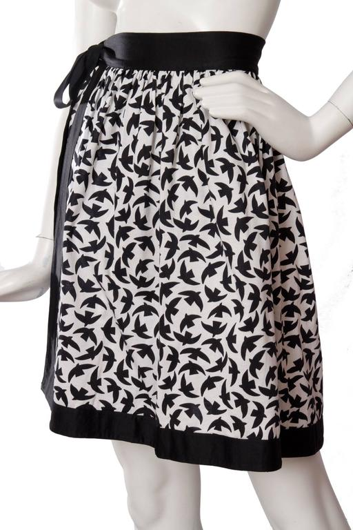A lovely 1980s Yves Saint Laurent cotton wrap skirt with black trim, tie belt and a slightly asymmetrical hemline. On the white base, the skirt has a black birds print, matching the all round trim.   The size of the skirt corresponds to a modern