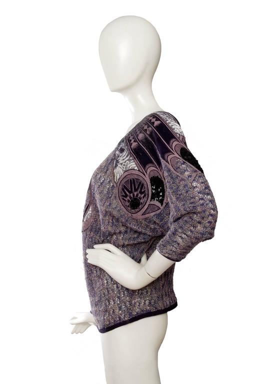 A fun knitted 1980s purple Roberto Cavalli off-shoulder blouse with elaborate patchwork detailing arrows the shoulders and down the front and back. The light purple colors of the loose knit brilliantly compliments the darker hues of the patchwork,