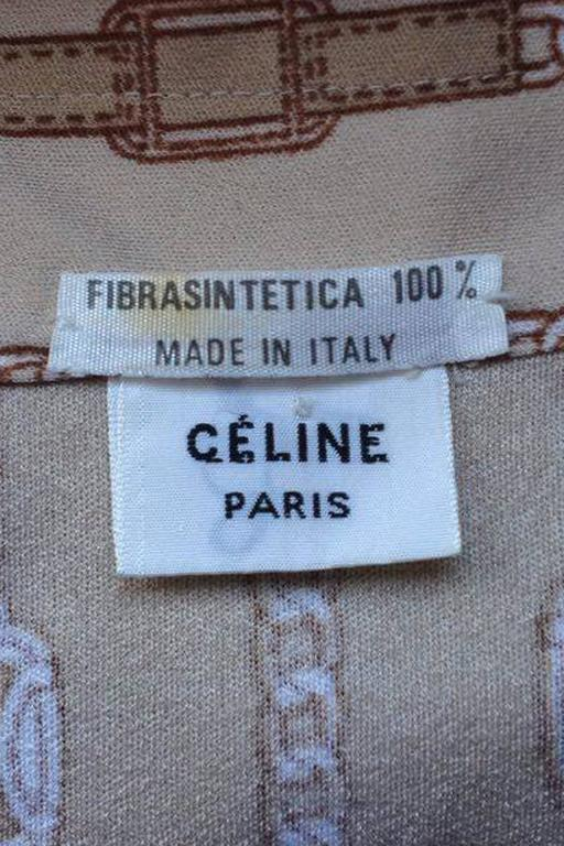 A 1970s beige Celine blouse with long tapered sleeves with two buttoned cuffs and a front buttoned closure. The gorgeous blouse features the iconic chain print with 'Celine' logo inserts which elongates the length by its vertical placement.   The