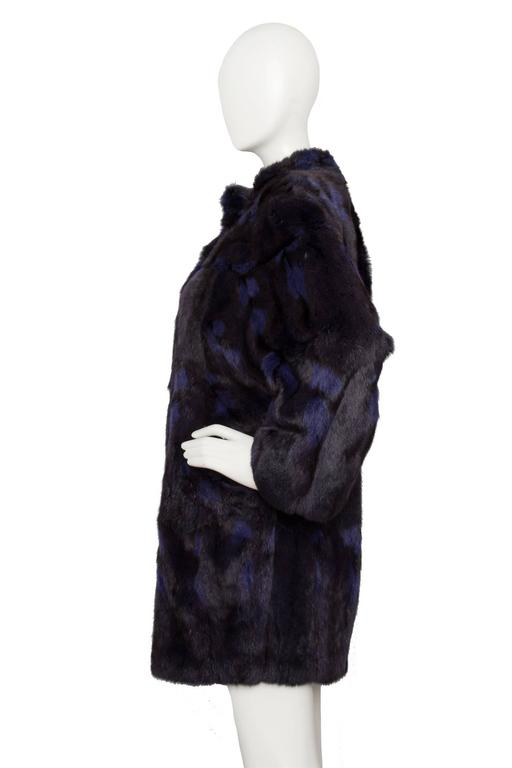 A glamorous 1980s Celine black dyed mink fur coat with blue streaks. The coat has side pockets, a front hook & eye closure as weel as two large buttons fastenings the top. A matching black lining is woven with 'Celine'.