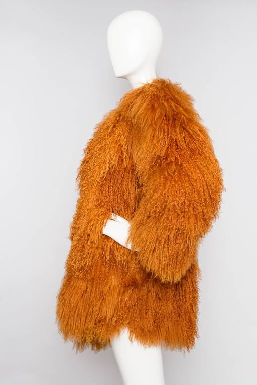 A stunning 1990s Yves Saint Laurent orange Mongolian lamb fur coat with a round neckline and a front hook button closure. The glamorous coat has exaggerated shoulders, side pockets and is fully lined in matching brown silk with jacquard YSL logo