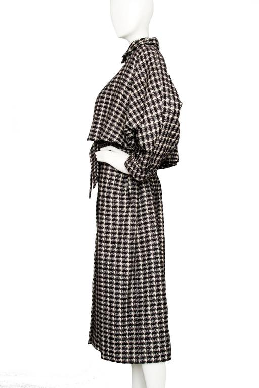 An incredible 1980s capped Lanvin tartan wool coat with wide sleeves and an optional belt that can be worn to define the waistline. The black and white coat buttons down the front with large black plastic buttons.  The size of the coat corresponds