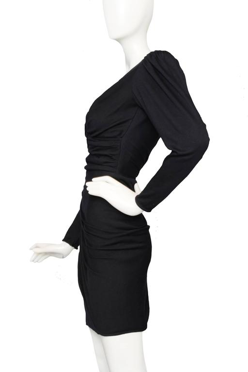 A fitted 1980s black Ungaro draped cocktail dress with long tapered sleeves, exaggerated shoulders with structured shoulder padding, and asymmetrical ruching across a tightly fitted miniskirt. The dress has incredible pleating detail at the top