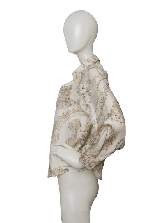 A fitted 1970s printed light grey Hermès silk shirt with a short bodice, long sleeves with one-button cuffs and a full front button down closure. The shirt has a classic Hermés print in light brown, beige and white with black and grey accents.